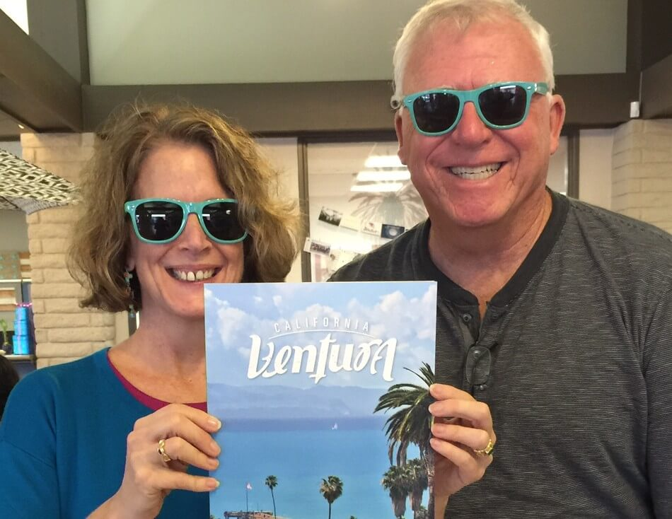 Two volunteers holding a visitor guide